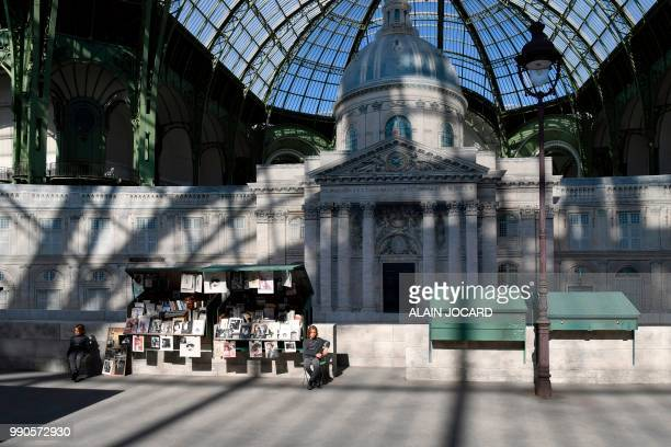German fashion designer Karl Lagerfeld's godson Hudson Kroenig sits next to a replica of Parisian openair book stalls and the French Institute before...