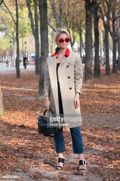 German fashion influencer Caro Daur wears a Rochas coat Manolo Blahnik shoes Loewe bag Calvin Klein jeans Oscar de la Renta earring and Vintage...