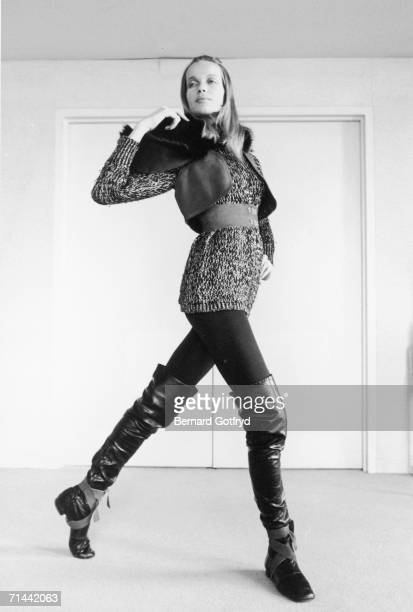German fashion model Veruschka walks past a doorway dressed in a long knit shirt vest and thinglength boots New York New York March 1968