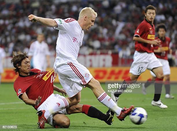 German FC Bayern Munich Christian Lell keeps the ball against Japan's Urawa Reds midfielder Takahito Soma during their international friendly match...
