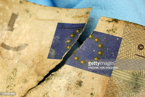 A German Federal Bank employee holds a flooddamaged five euro banknote with the broken symbol of the European Union at the counterfeit analysis...