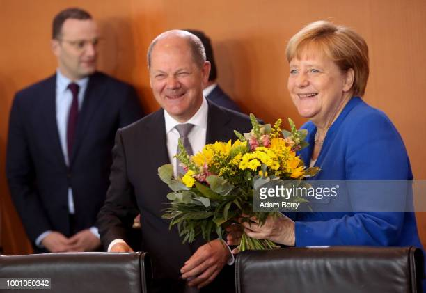 German Federal Chancellor Angela Merkel receives flowers for her 64th birthday the previous day from Finance Minister and Vice Chancellor Olaf Scholz...