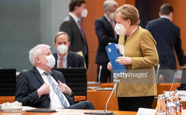 German Federal Minister of the Interior, Building and Community Horst Seehofer speaks with Chancellor Angela Merkel ahead of the weekly government...