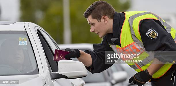 A German Federal Police officer gives the passport back to a car driver as he controls vehicles coming from Austria in Freilassing at the...
