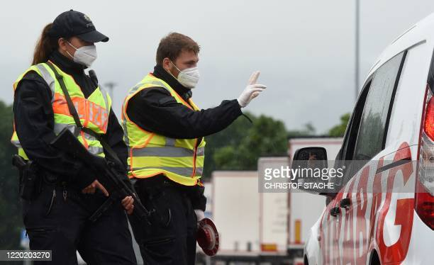 German federal police officers wearing face masks control a car driver at a chekcpoint of the German federal police at the border crossing between...
