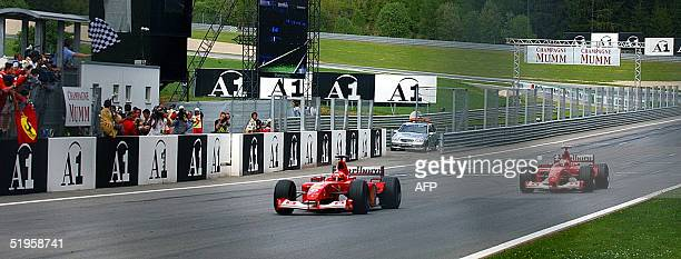 German Ferrari driver Michael Schumacher crosses the finish line ahead of his teammate Rubens Barichello on the Spielberg racetrack 12 May 2002 at...
