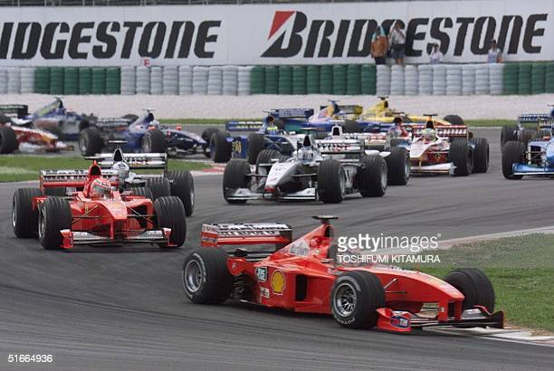 German Ferrari driver Michael Schumacher leads the pack exiting the chicanes after the start of the Malaysian Grand Prix at the Sepang International...