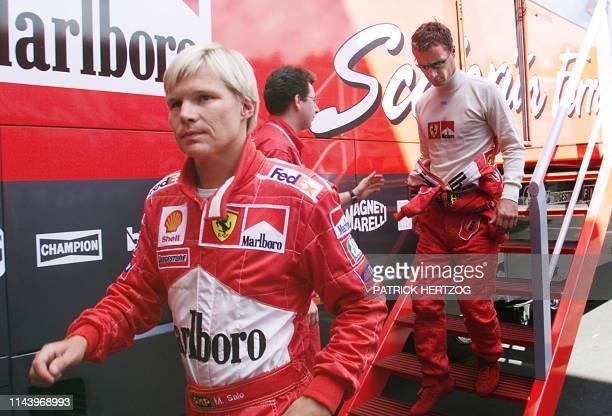 German Ferrari driver Michael Schumacher's substitute Mika Salo of Finland and teammate Eddie Irvine of Northern Ireland leave the Ferrari motorhome...