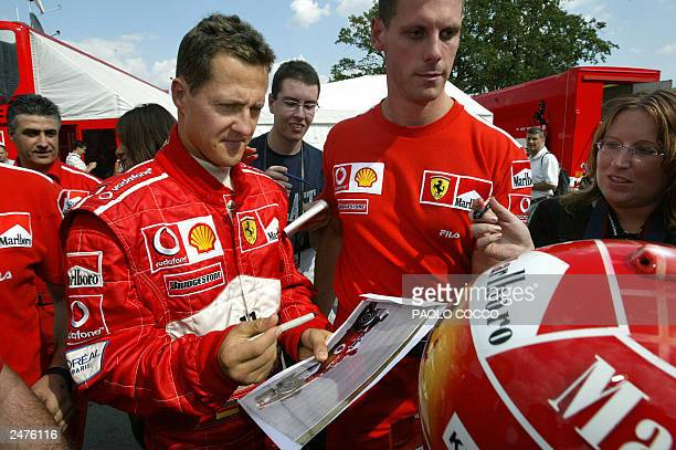 German Ferrari Formula One driver Michael Schumacher signs autographs during the first day of tests at Monza's track 02 September 2003 outside Milan...