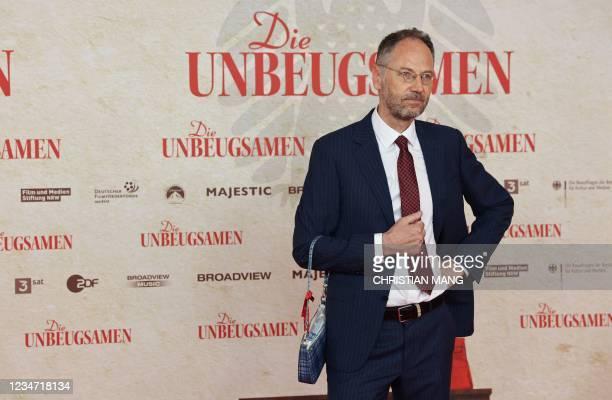 """German film director Torsten Koernerat poses with a ladies' bag ahead of the premiere of his documentary movie """"Die Unbeugsamen"""" at Delphi Cinema in..."""
