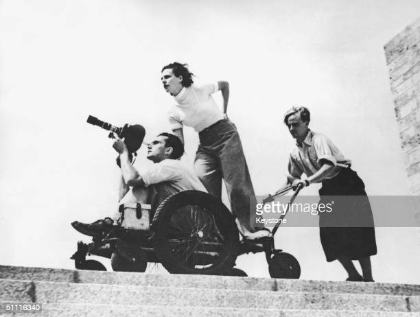 German film maker Leni Riefenstahl and cameraman Walter Frentz being wheeled along by an assistant at the 1936 Berlin Olympics