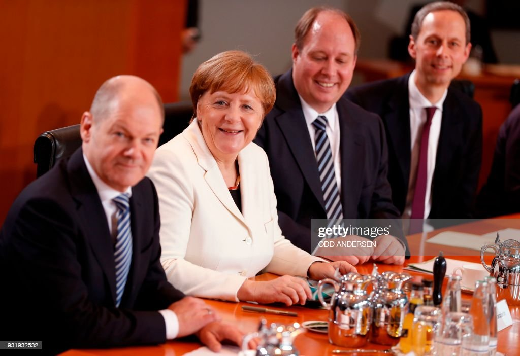 German Finance Minister and Vice-Chancellor Olaf Scholz, German Chancellor Angela Merkel and German Chief of Staff Helge Braun smile at the start of the first cabinet meeting of the newly appointed ministers at the chancellery in Berlin on March 14, 2018. German Chancellor Angela Merkel, bruised by half a year of post-election coalition haggling, was Wednesday narrowly confirmed by parliament to her fourth and likely final term at the helm of Europe's biggest economy. / AFP PHOTO / Odd ANDERSEN