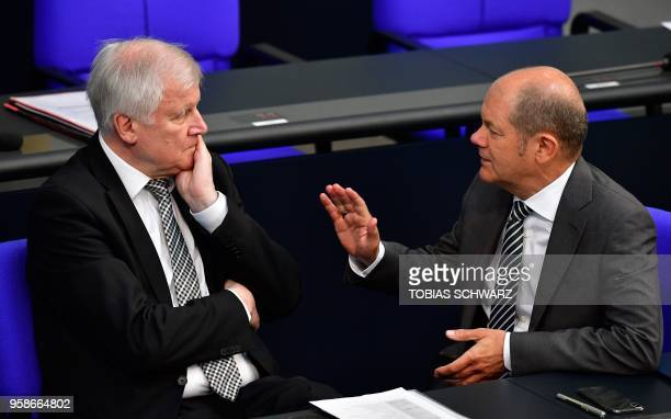 German Finance Minister and ViceChancellor Olaf Scholz talks with German Interior Minister Horst Seehofer as they attend a session of the Bundestag...