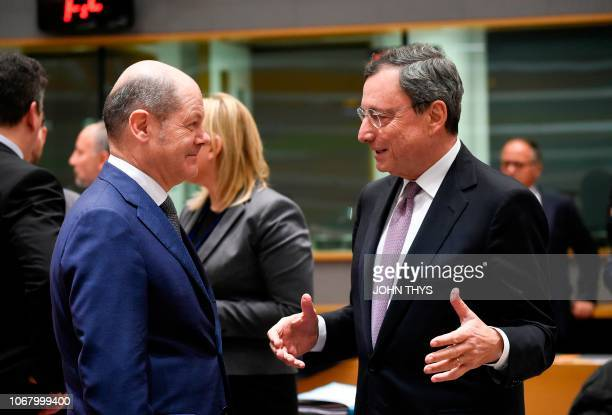 German Finance Minister Olaf Scholz talks with President of the ECB Mario Draghi during an Eurogroup meeting at the EU headquarters in Brussels on...