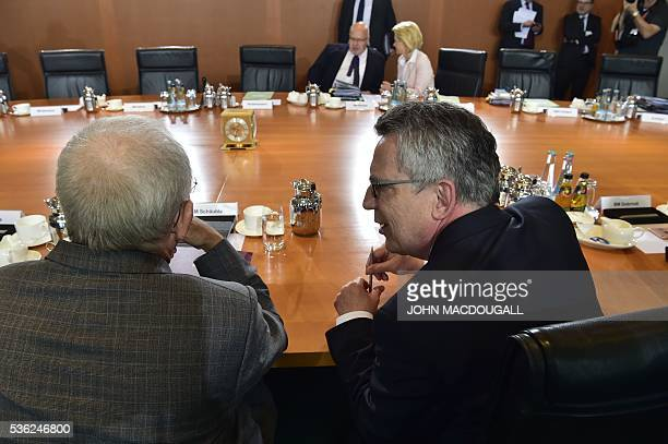 German Finance Minister Wolfgang Schaeuble and German Interior Minister Thomas de Maiziere chat prior to the weekly cabinet meeting in Berlin on June...
