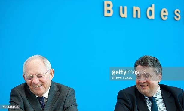 German Finance Minister Wolfgang Schaeuble and Vice Chancellor and Economic Minister Sigmar Gabriel laugh during a news conference at the Haus der...