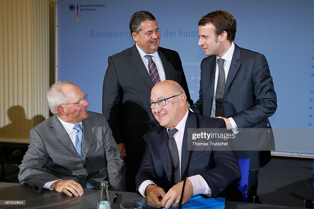 German Finance Minister Wolfgang Schaeuble, German Economy Minister and Vice Chancellor Sigmar Gabriel, French Finance Minister Michel Sapin, and French Economy and Industry Minister Emmanuel Macron, chats after a press conference on October 20, 2014 in Berlin, Germany. The Ministers discussed the economic and financial cooperation policy between Germany and France.