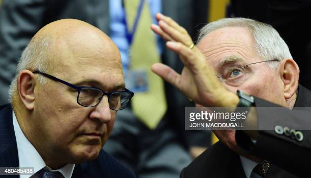 German Finance Minister Wolfgang Schaeuble gestures as he speaks with French Finance Minister Michel Sapin during a meeting of the Eurogroup finance...