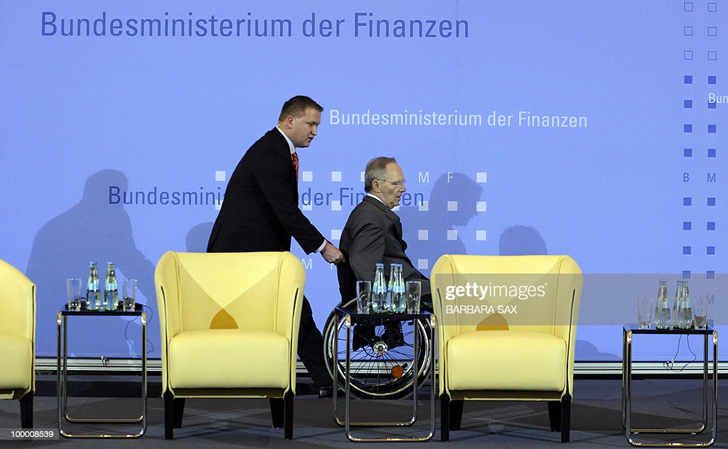 German Finance Minister Wolfgang Schaeuble is pushed on his wheelchair to the speaker's desk during a conference on financial regulation on May 20, 2010 at the Finance Ministry in Berlin. Merkel said during the conference she would lead a campaign for a tax on financial markets at the next meeting of the Group of 20 developed economies in June 2010 and called for international support.