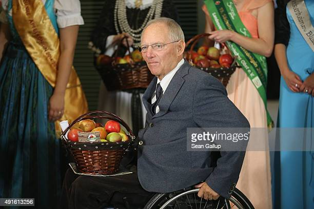 German Finance Minister Wolfgang Schaeuble receives a basket of apples before the weekly government cabinet meeting on October 7 2015 in Berlin...