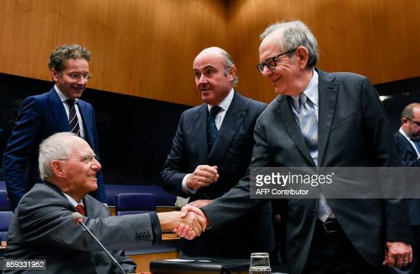 German Finance Minister Wolfgang Schaeuble shakes hand with Italian Finance Pier Carlo Padoan as Dutch Finance Minister and President of the...