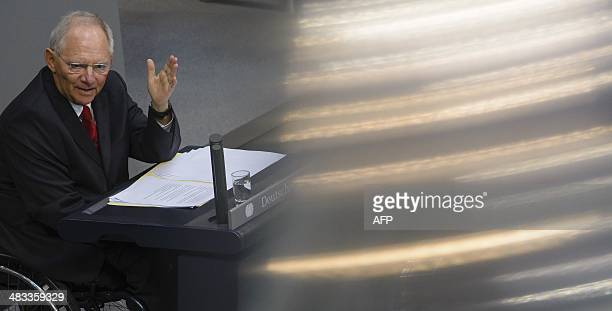 German Finance Minister Wolfgang Schaeuble sits on his wheelchair as he delivers a speech to present his draft budget for 2014 to lawmakers during a...