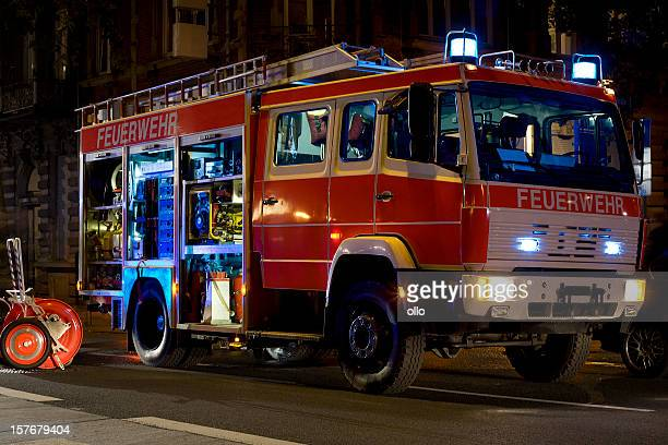 german firefighter truck in action at night - firetruck stock photos and pictures