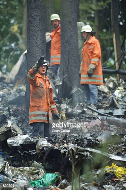 German firefighters stand among the wreckage of a DHL Boeing 757 cargo plane July 2, 2002 in a forest near the town of Taisersdorf, Germany. The...