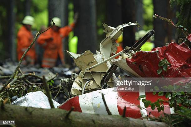 German firefighters stand behind the torn fuselage of a DHL Boeing 757 cargo plane July 2 near the southern German village of Taisersdorf. The...