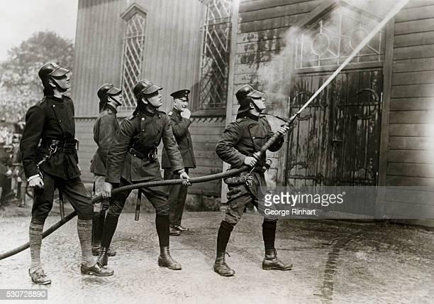 German firemen training the hose on a church fire Undated photograph