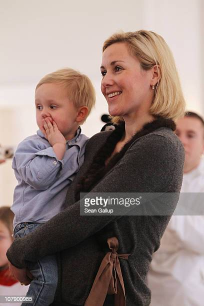 German First Lady Bettina Wulff carries her son Linus at a reception for child Epiphany carolers at Bellevue Presidential Palace on January 6, 2011...
