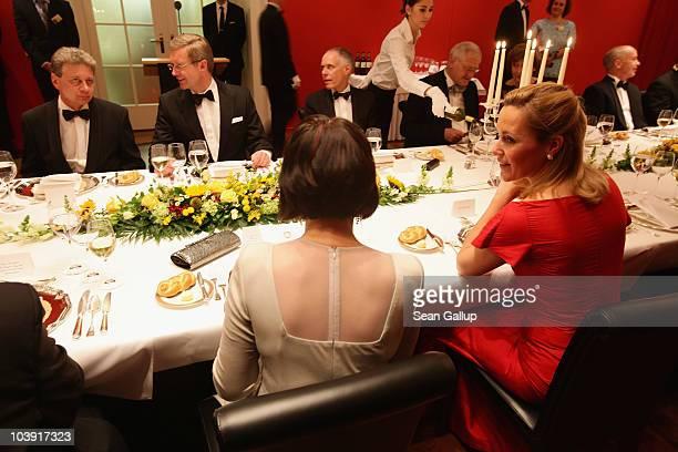 German First Lady Bettina Wulff chats with Swiss President Doris Leuthard as German President Christian Wulff chats with Mrs Leuthard's husband...