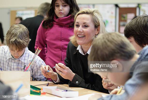 German First Lady Bettina Wulff sits together with scholars during her visit at the Lietzensee school on January 18 2011 in Berlin Germany Bettina...