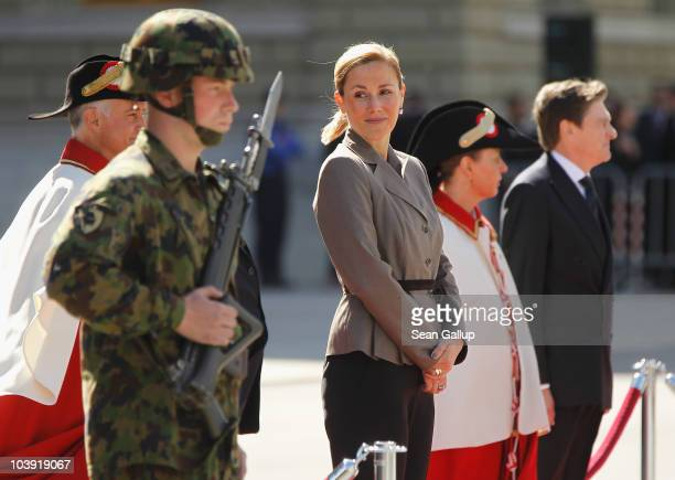 German First Lady Bettina Wulff stands waiting while her husband President Christian Wulff reviews a gaurd of honour on the first day of a twoday...