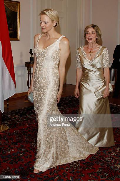 German First Lady Daniela Schadt steps on the dress of Princess Charlene of Monaco upon their arrival for the gala dinner at Schloss Bellevue Palace...