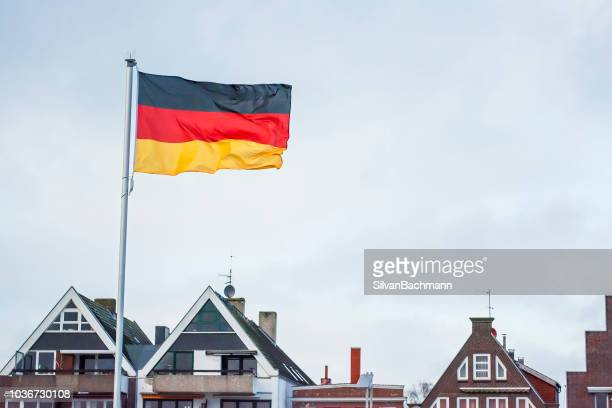 german flag and rooftops, travemunde, lubeck, germany - german flag stock pictures, royalty-free photos & images