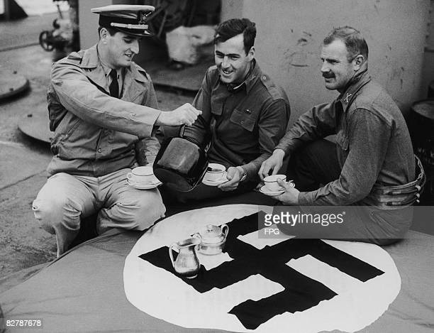 German flag captured at Hell's Corner in Carentan, France, doubles as a tablecloth for a US Coast Guard officer and two army officers on board a...