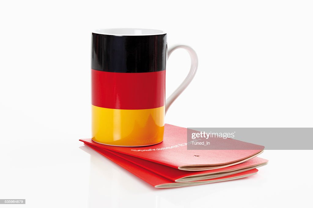 German flag cups with bank book on white background : Stock Photo