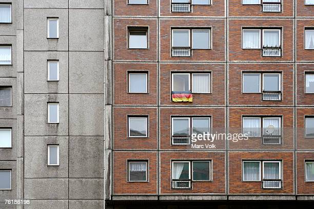 A German flag hanging from the window of an apartment