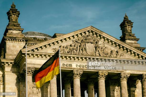 german flag waving against reichstag building - german flag stock pictures, royalty-free photos & images