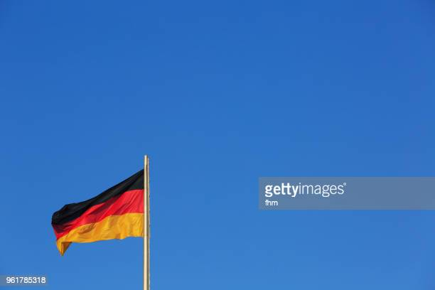 german flag with blue sky (berlin, germany) - allemagne photos et images de collection