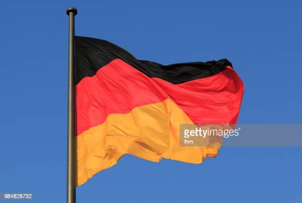 german flag with blue sky (berlin, germany) - german flag stock pictures, royalty-free photos & images