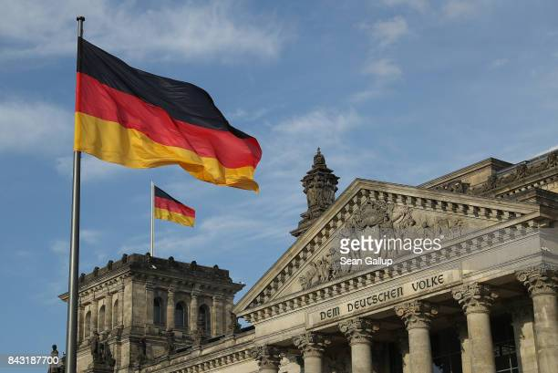German flags fly over the Reichstag seat of the Bundestag on September 4 2017 in Berlin Germany Germany is scheduled to hold federal elections on...