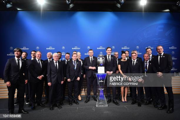 German Football Association president Reinhard Grindel and members of the German bid delegation pose with the UEFA Euro trophy after it was announced...