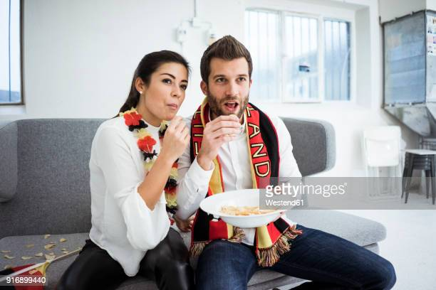 German football fan couple sitting on couch eating chips and watching Tv
