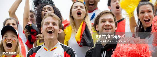 german football fans cheering at football match - northern european stock photos and pictures