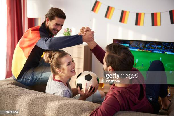 German football fans watching Tv and cheering
