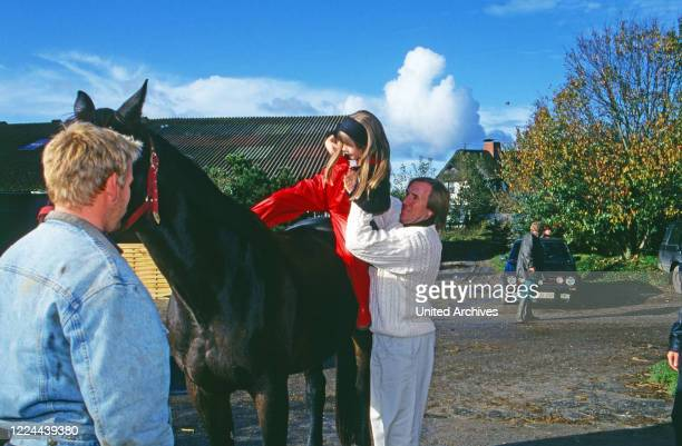 German football player sits daughter Alana in the saddle while visiting a horse stable at Sylt island Germany 1993