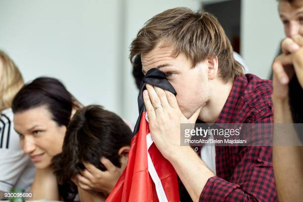 german football supporter covering face with flag while watching match at home - derrota imagens e fotografias de stock