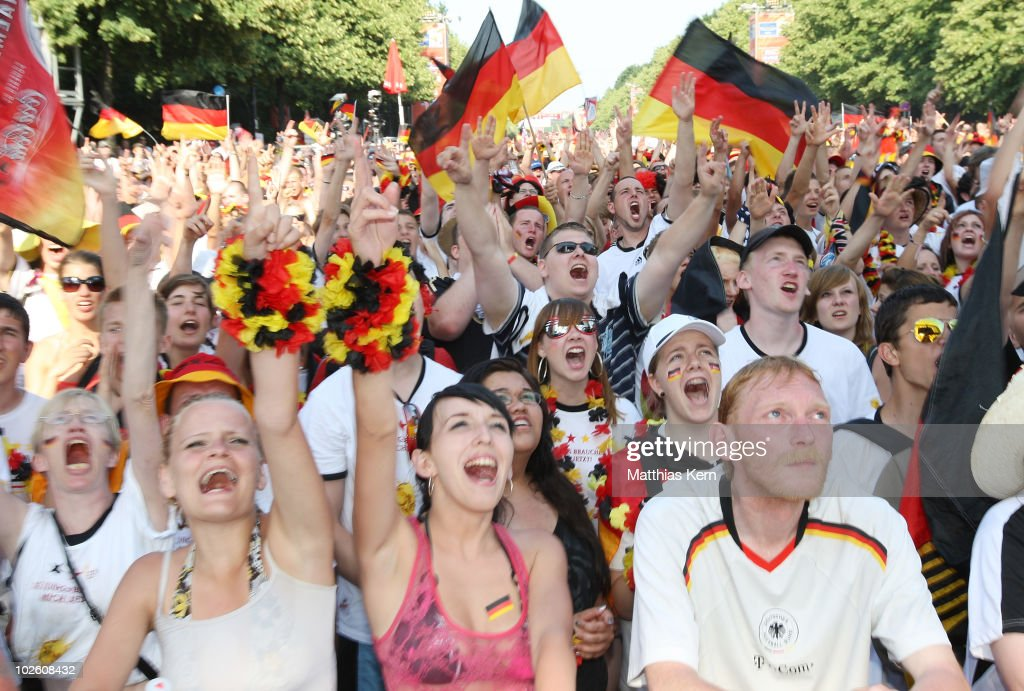 German football supporters jubilate after their team score a goal while watching the 2010 FIFA World Cup quarter final match between Germany and Argentina at a live public viewing on a large screen monitor at FIFA Fanmeile on July 3, 2010 in Berlin, Germany.